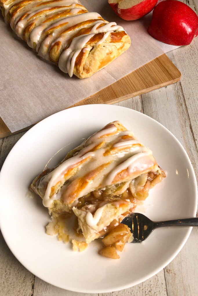 Slice of Apple Cinnamon Strudel on a plate with a fork.  Apple strudel in the background with glaze and red apples.