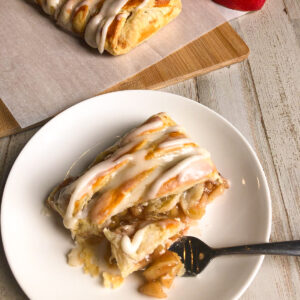 Apple cinnamon strudel with vanilla glaze on a white plate with a fork