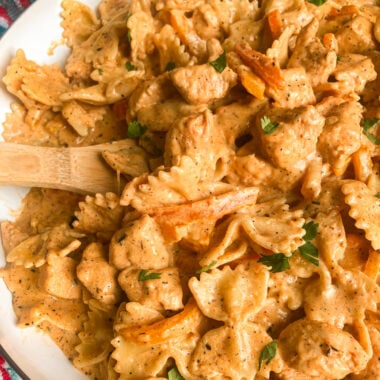 cajun chicken pasta in a skillet with a wooden spoon and parsley for garnish