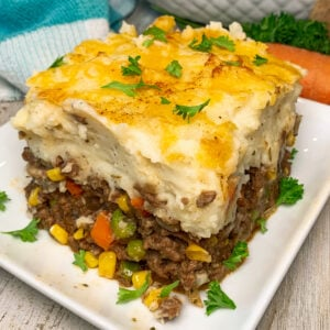 Close up of Shepherd's pie on a white plate garnished with fresh parsley.