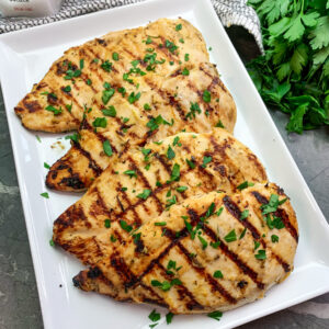 Honey mustard grilled chicken on a white plate garnished with fresh chopped parsley.