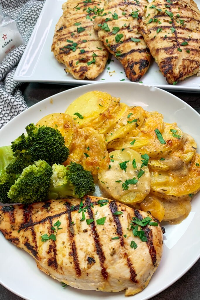 Honey mustard grilled chicken on a plate. Served with scalloped potatoes and broccoli.