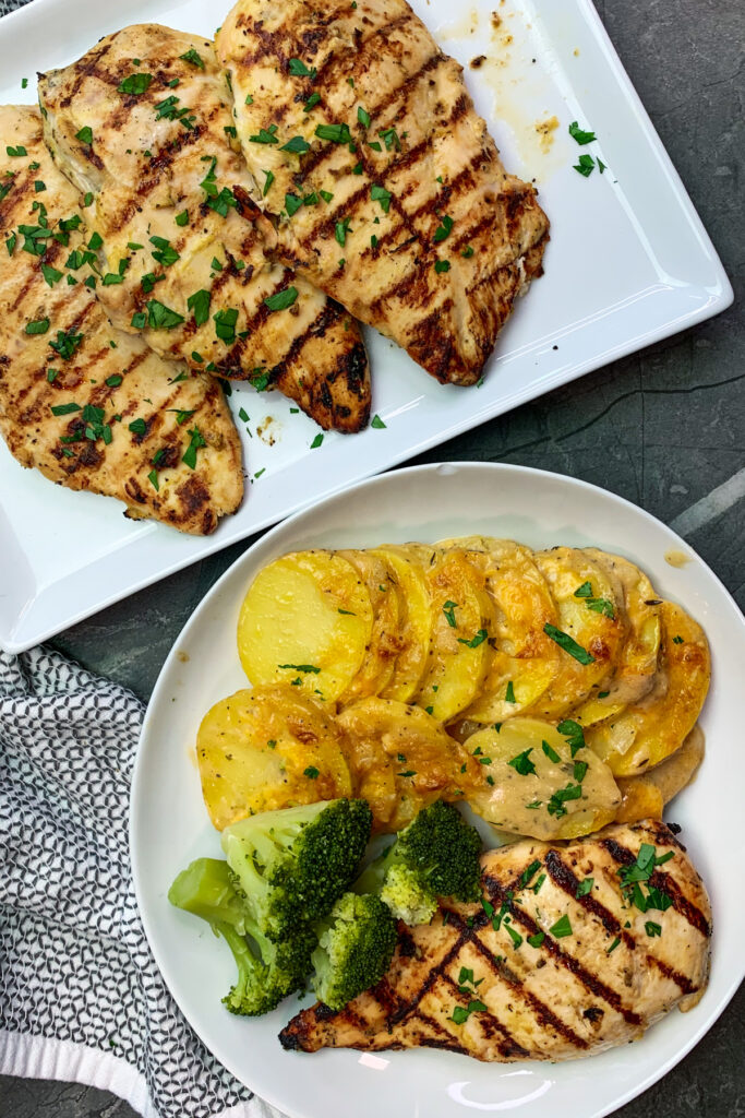 Completed recipe image of garlic dijon grilled chicken on a white plate served with a side of scalloped potatoes.