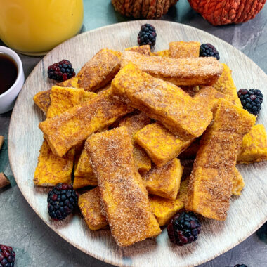 Pumpkin churro French toast sticks stacked up on a plate.