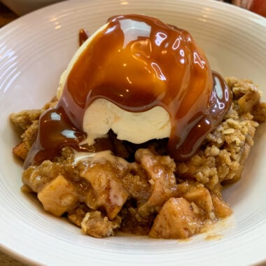 Close up of apple crisp with a scoop of ice cream on top and caramel sauce in a white bowl.