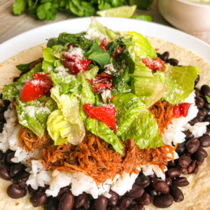 Cafe Rio Sweet Pork Recipe served on a flour tortilla with rice, black beans, shredded lettuce and Pico de Gallo.