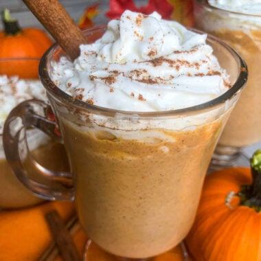 Pumpkin White Hot Chocolate with whipped cream and cinnamon stick in a glass mug.
