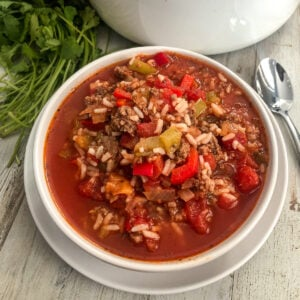 stuffed pepper soup in a white bowl with a silver spoon and fresh parsley for garnish.