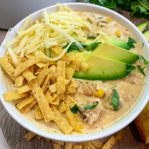 Close up of white chicken chili garnished with avocado, cheese, and tortilla strips.