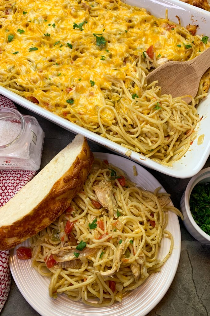 Best chicken spaghetti casserole on a white plate. Served with a slice of cheese bread.