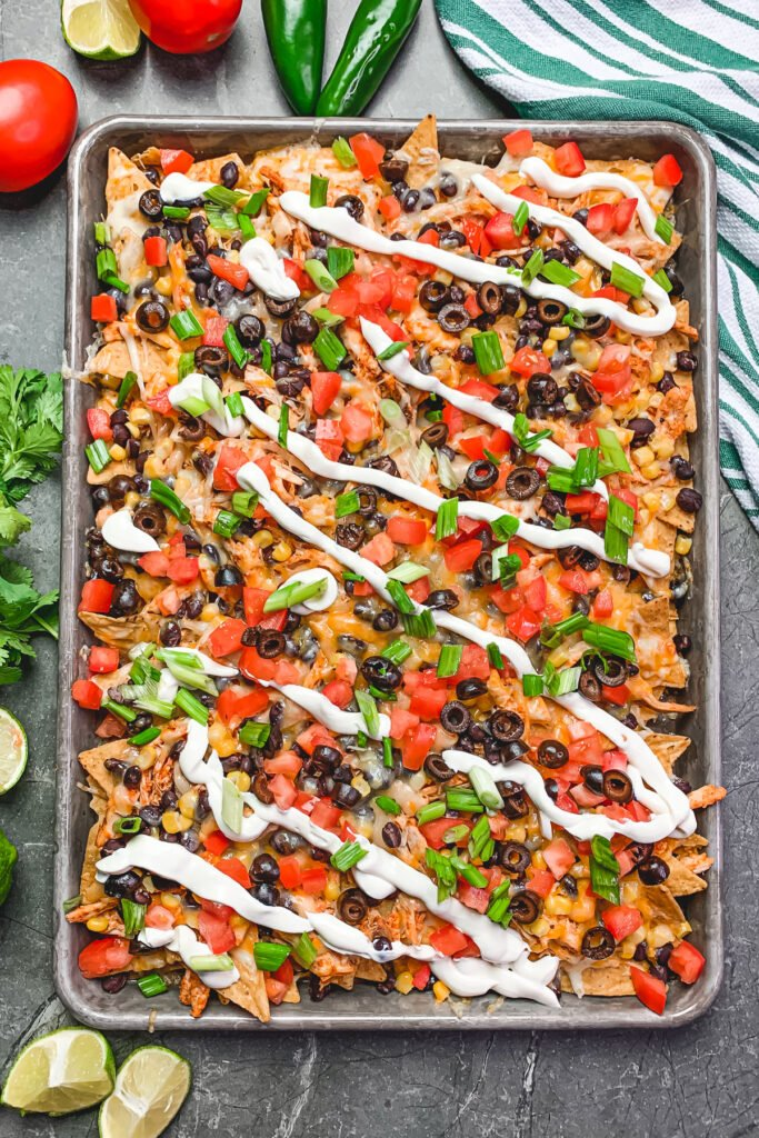 Overhead pic of loaded nachos with, fresh jalapenos, limes, and tomatoes around them.