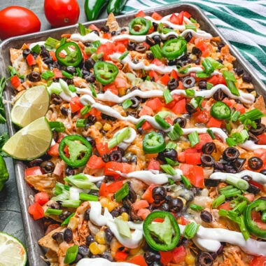 Close up of sheet pan chicken nachos with all the toppings and garnished with limes.