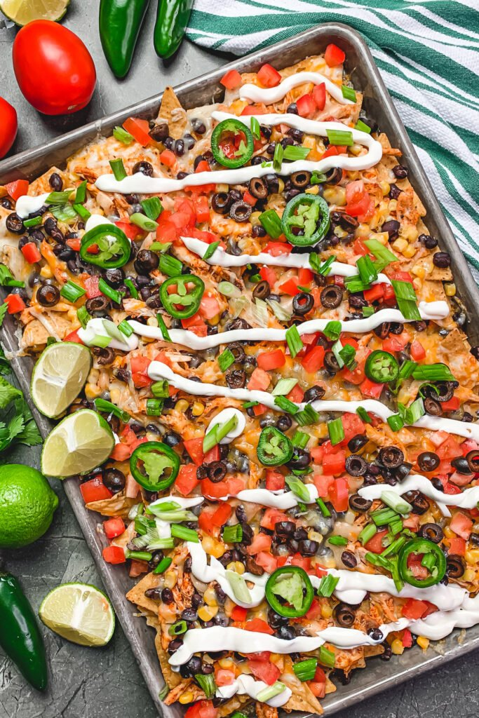 Overhead view of sheet pan chicken nachos garnished with jalapenos, green onions, and fresh limes.