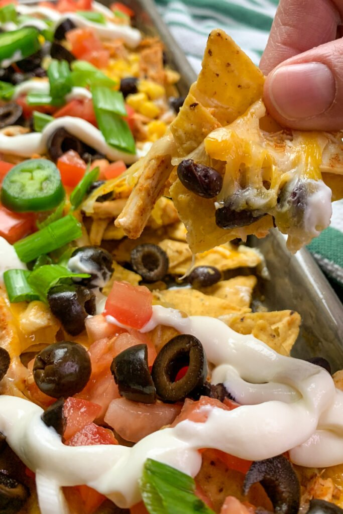Close up of baked chicken nachos topped with chicken, beans, corn, tomatoes, olives, jalapenos, cheese, and green onions.