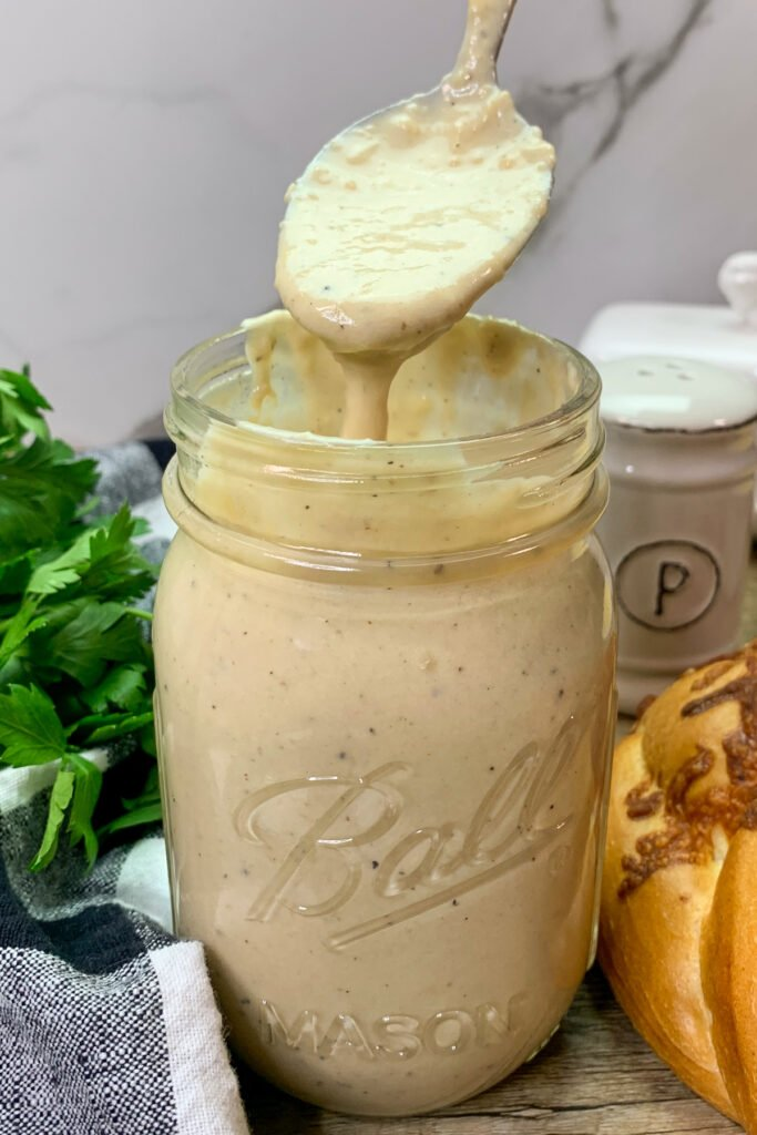 Close up pic of homemade alfredo sauce in a mason jar with the creamy sauce dripping from a spoon.