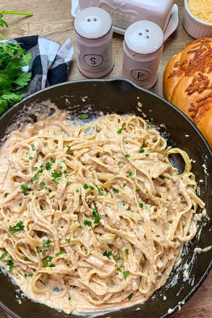 Close up of Fettucine covered in creamy Alfredo sauce and garnished with fresh chopped parsley.