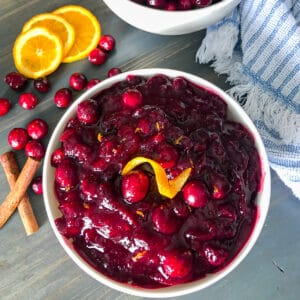 homemade cranberry sauce in a serving dish with orange slices, fresh cranberries, and cinnamon sticks for garnish