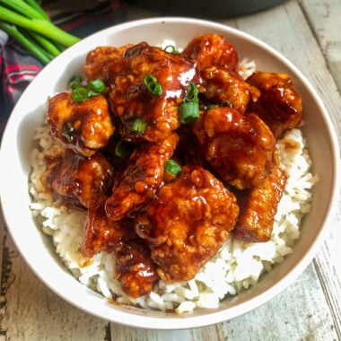 General Tso's Chicken in a serving bowl with white rice and green onions for garnish
