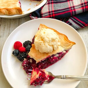 easy mixed berry pie on a white plate with berries on the side and topped with ice cream