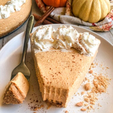 No-Bake Pumpkin Cheesecake on a serving plate with a white pumpkin and cheesecake in the background