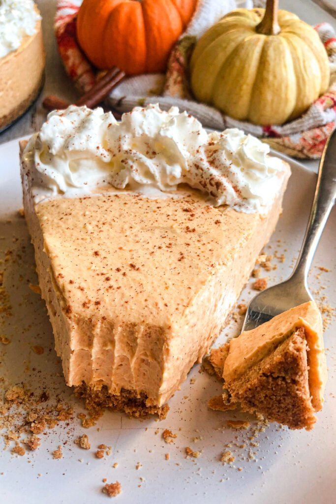no-bake pumpkin cheesecake on a serving plate topped with whipped cream.