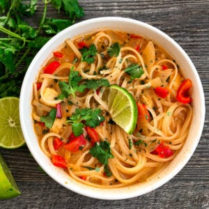 Thai Red Curry Soup in a serving bowl with fresh cilantro and a slice of lime for garnish