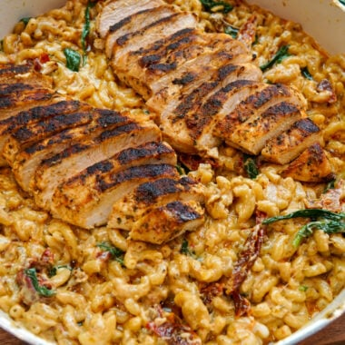 Close up of Tuscan chicken mac and cheese with sun-dried tomatoes and spinach.