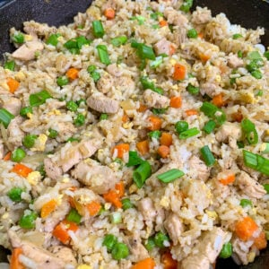 Chicken fried rice in a skillet garnished with green onion.