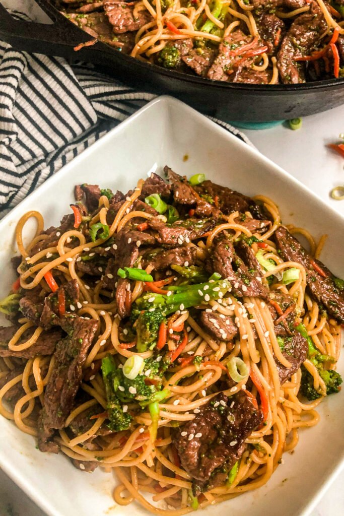 beef and broccoli Lo Mein in a serving dish garnished with sesame seeds and sliced green onions