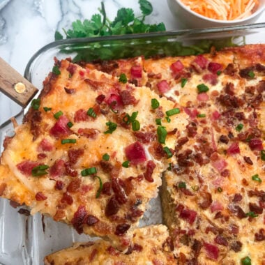 overnight breakfast casserole garnished with sliced green onions and shredded cheddar cheese