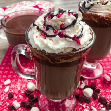 Peppermint hot chocolate served with whipped cream, chocolate drizzle, and chopped candy canes for garnish.