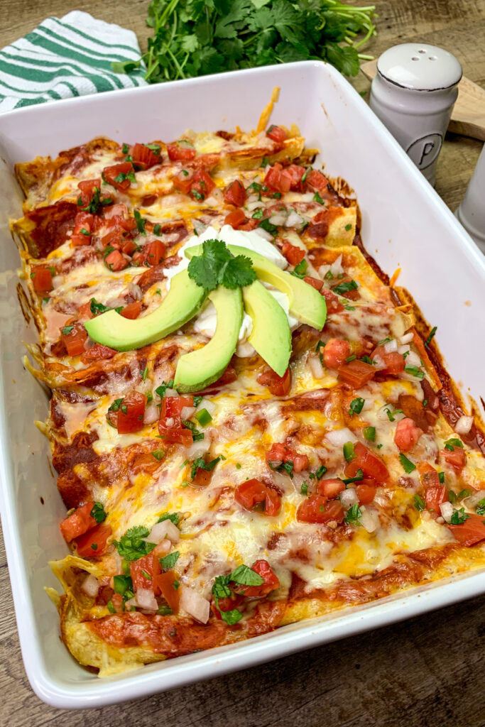 Homemade chicken enchiladas in a white baking dish. Topped with sour cream and sliced avocados.