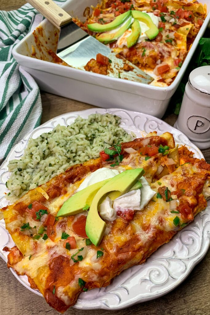 Easy chicken enchiladas on a plate and garnished with pico de gallo, sour cream, and avocado.