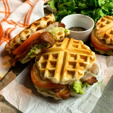 Close up of a BLT waffle cheese sandwich on a piece of parchment paper.
