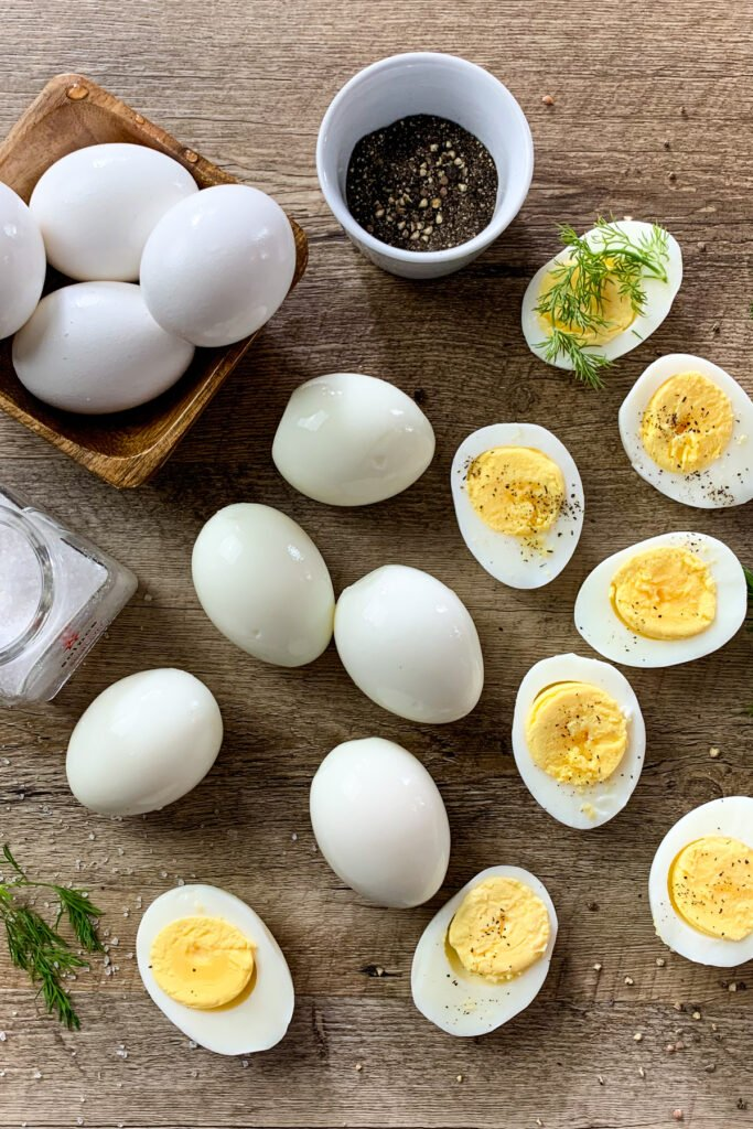 How to hard boil eggs so they are easy to peel. Boiled eggs cut in half on a cutting board.