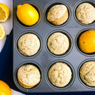 Lemon Poppy Seed Muffins in a muffin tin with lemons as a garnish