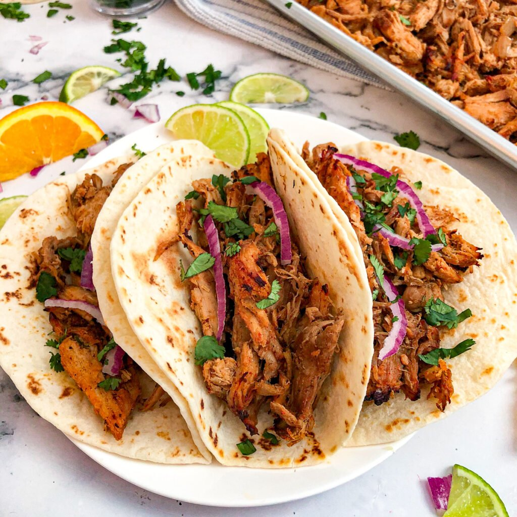 Crockpot carnitas served in flour tortillas with lime wedges, red onion, and cilantro for garnish