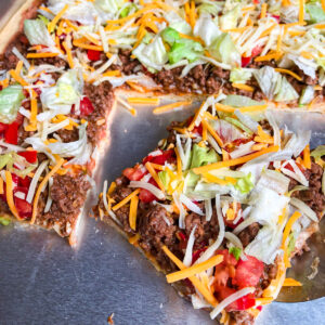Homemade taco pizza recipe topped with chopped tomatoes, shredded lettuce, and shredded cheese
