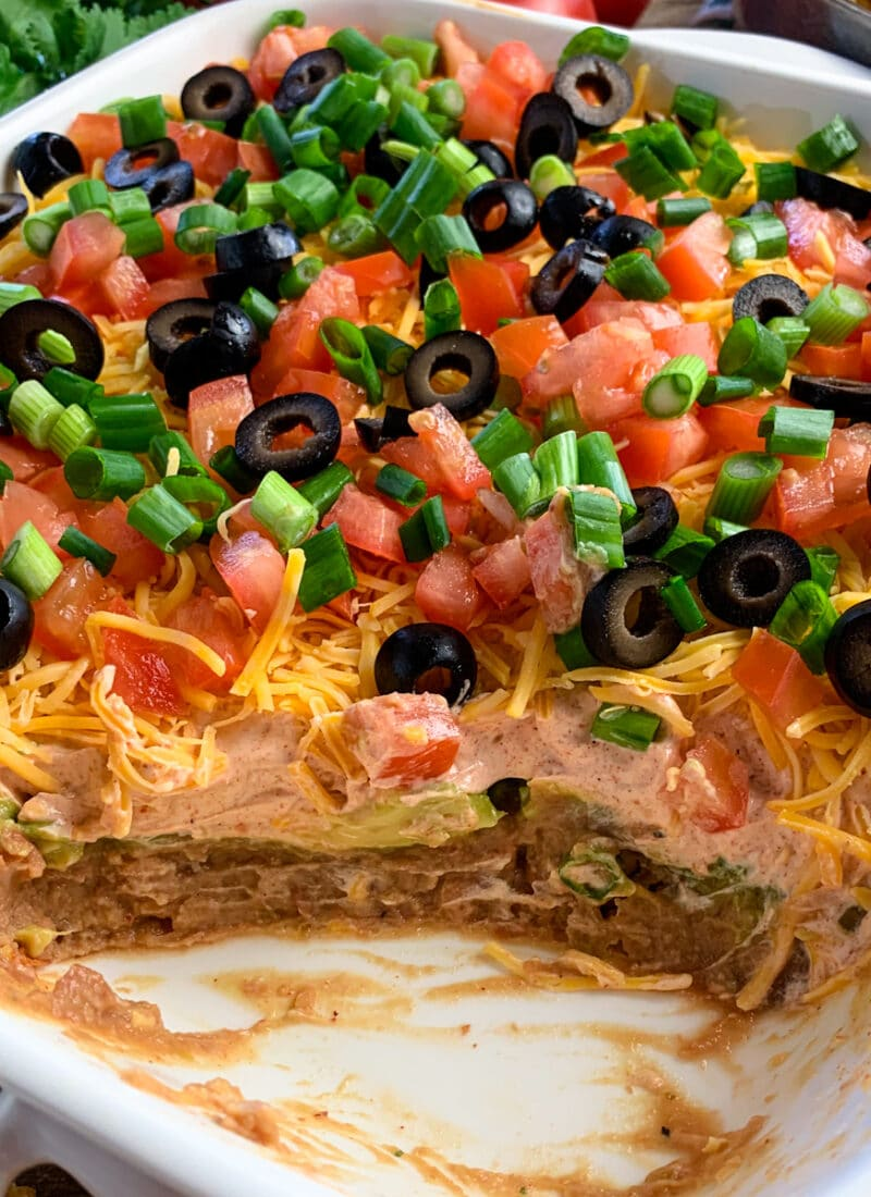 7 layer dip made with refried beans, salsa, sour cream, guacamole, cheese, olives, tomatoes, and green onions.