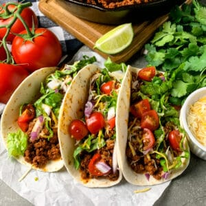 Three ground beef tacos with cheese, lettuce, tomatoes, and red onion.