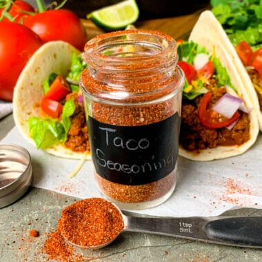 Homemade taco seasoning in a small glass jar and some in a measuring spoon.