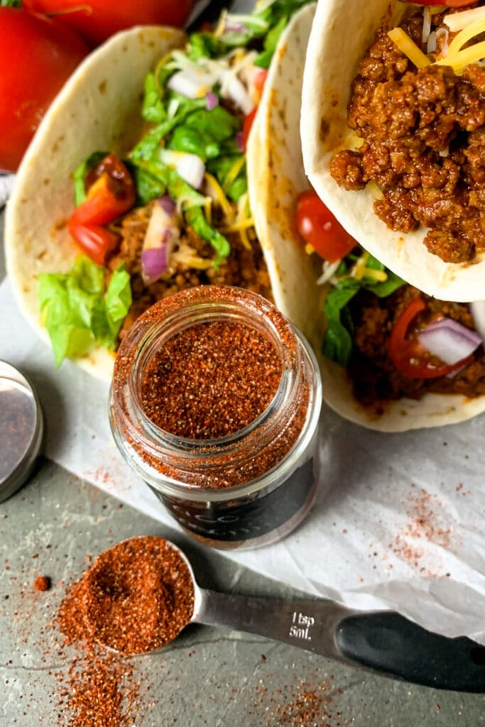 Homemade taco seasoning in a jar and in a taco to show off the color of the taco meat.