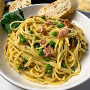Close up of pasta carbonara in a white bowl and garnished with bread.