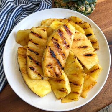 Easy grilled pineapple piled on a white serving plate
