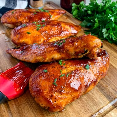 Baked BBQ chicken breasts on a wood cutting board garnished with fresh parsley.