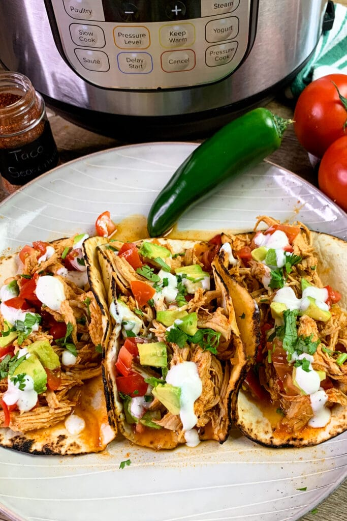 Instant Pot chicken tacos on a plate with a pressure cooker in the background.