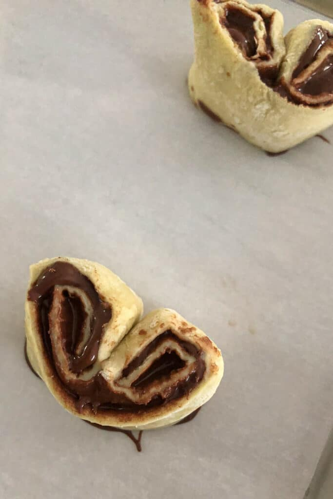 Nutella puff pastry rolled up and placed on a sheet pan