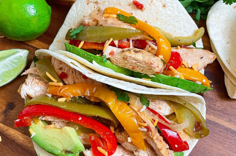 slow cooker chicken fajitas served in tortillas with lime, cheese, and cilantro