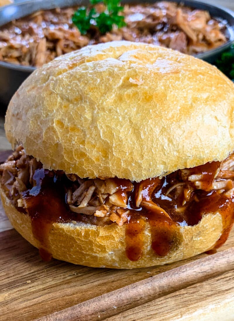 Instant Pot root beer pulled pork on a bun with extra bbq sauce.