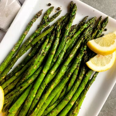 Grilled asparagus on a white plate with lemon slices.